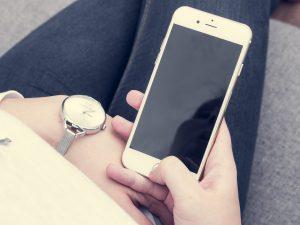 תמונה של חלק מאישה שמחזיקה טלפון ביד